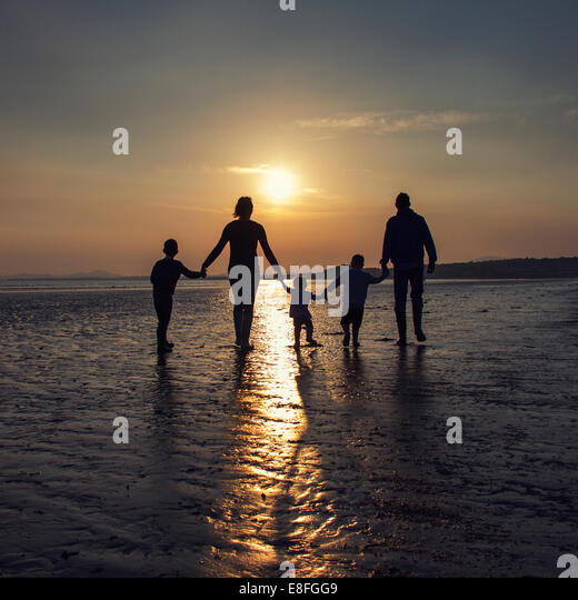 Silhouette of family holding hands on the beach at sunset - Stock-Bilder