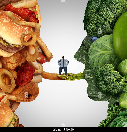 Eating options food health issue as an obese man standing on a bridge between junk food and fruit and vegetable - Stock Image