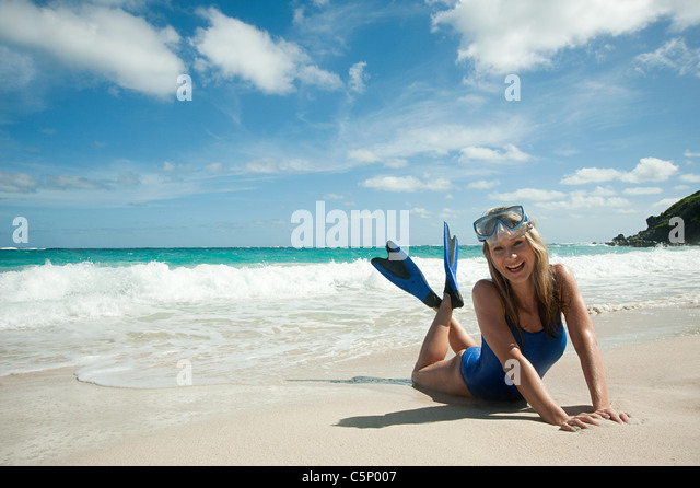 Woman at water's edge, Mustique, Grenadine Islands - Stock Image