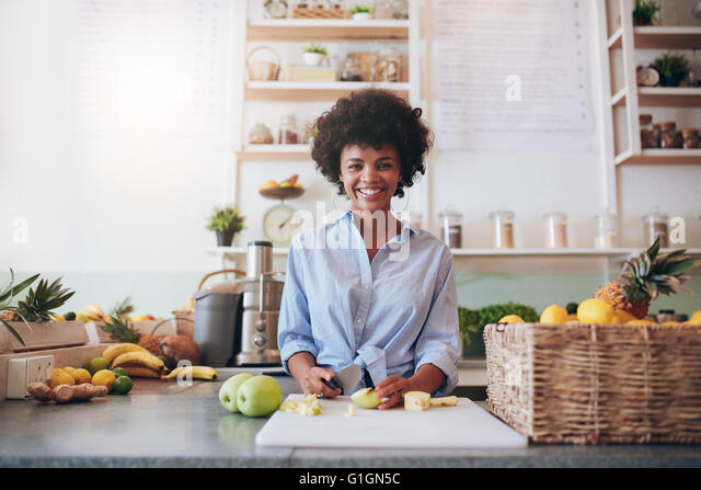Portrait of beautiful young african woman standing behind the bar counter and chopping fresh fruits. Woman working - Stock Image