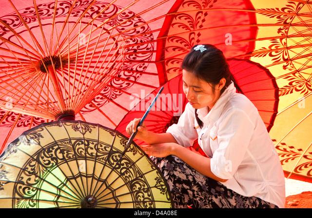 Young woman painting decorative designs at umbrella workshop in Old Bagan, Myanmar (Burma) - Stock-Bilder