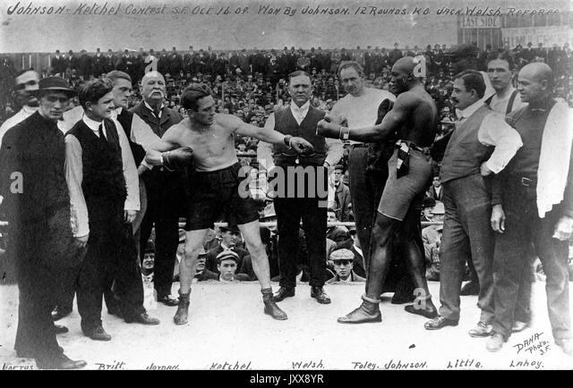 Boxers Stanley Ketchel (center left) and Jack Johnson (center right) stand in the ring before their famous match, - Stock Image