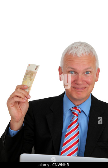 Senior Businessman with money and laptop laughing - Stock Image