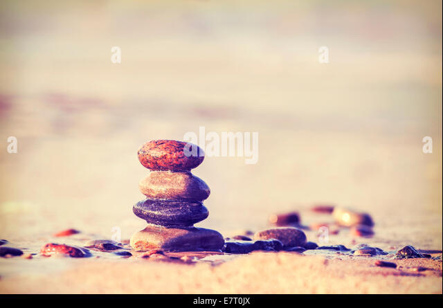 Vintage retro style image of stones on beach. - Stock Image