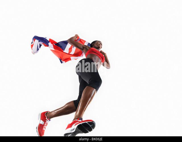Female athlete running with union jack - Stock Image
