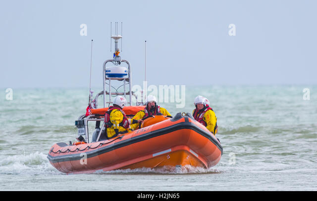 RNLI lifeboat crew on a small lifeboat rib at sea, about to enter the river estuary. - Stock Image