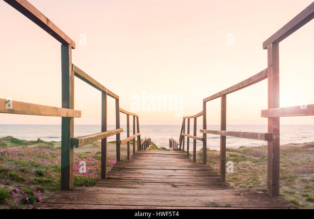 Boardwalk on a beach at sunset - Stock Image