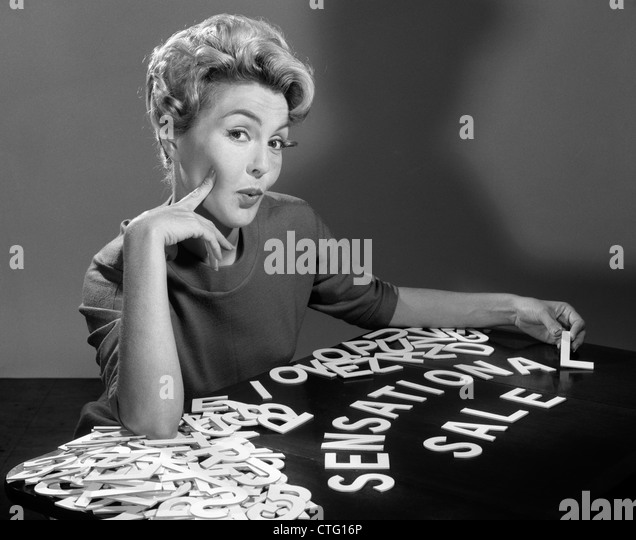 1950s 1960s PORTRAIT BLONDE WOMAN LOOKING AT CAMERA SPELLING OUT SENSATIONAL SALE WITH CUTOUT GRAPHIC DESIGN  LETTERS - Stock Image