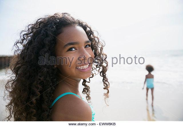 Portrait smiling girl curly brunette hair on beach - Stock Image