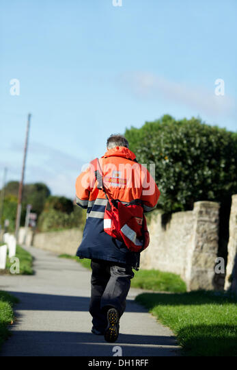 postman walking the street delivering mail - Stock Image