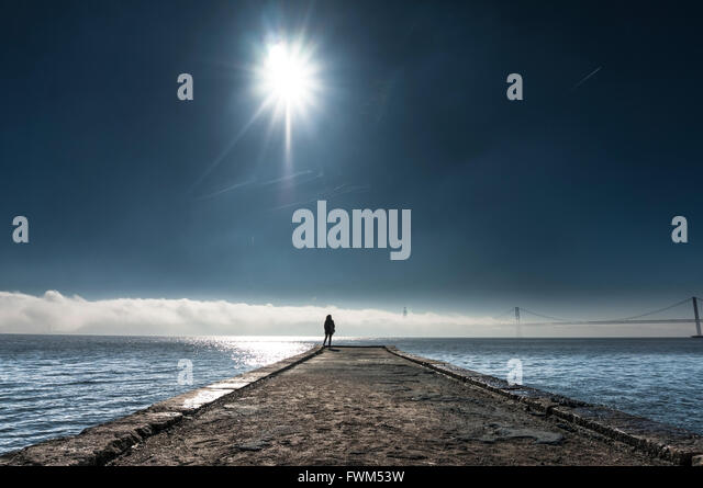 Distance View Of Person Standing On Pier Over Sea Against Sky - Stock Image