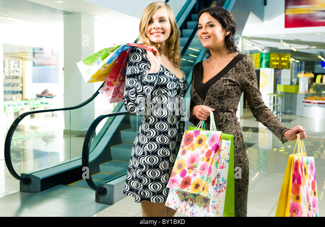 Image of young ladies looking at something with admiration in the shopping centre - Stock Image