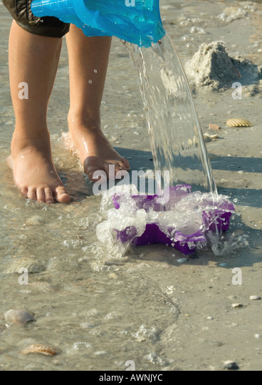 Child playing on beach, knee down - Stock Image