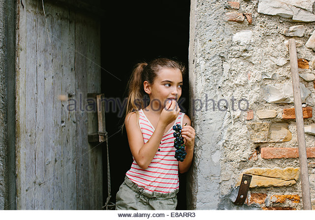 Girl eating grapes in barn doorway - Stock Image