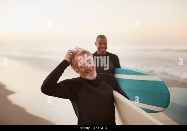 Older surfers carrying boards on beach - Stock Image