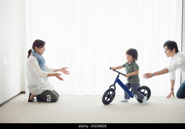 Parents with son learning to ride bicycle - Stock Image