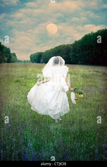a woman is running with a wedding dress over a field of flowers - Stock Image