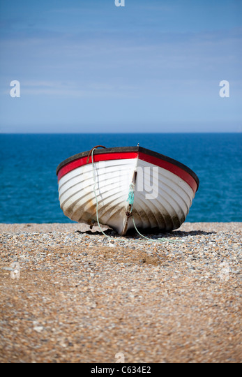 A rowing boat on the beach at Cley-next-the-Sea in North Norfolk, UK - Stock Image