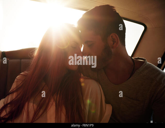 Romantic young couple sitting in back seat of a car. Young couple feeling romantic in back seat of a vehicle with - Stock-Bilder
