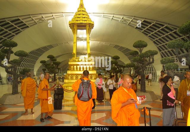 Bangkok Thailand Suvarnabhumi International Airport BKK terminal concourse gate area Buddhist shrine Asian man monk - Stock Image