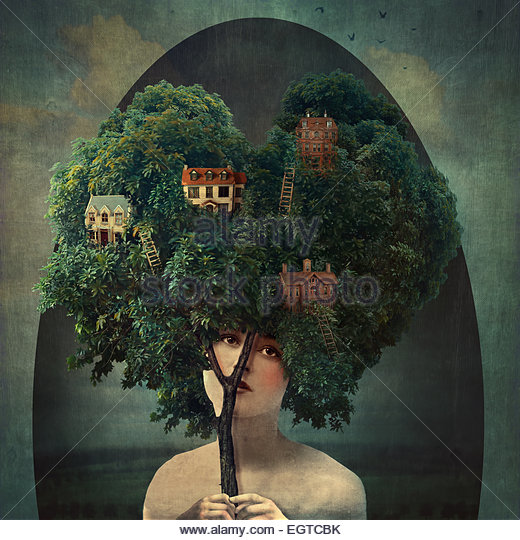 young woman holding a tree with houses - Stock Image