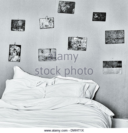 A bed surrounded by icon paintings, in an old house in the le Marche region of Italy. - Stock Image