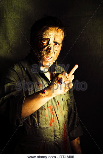 A walking dead zombie with decaying and rotting flesh gives a fingers up sign marking or singling out a person for - Stock Image
