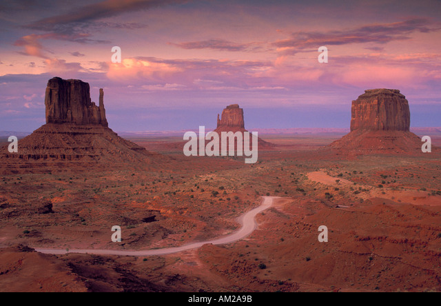 Dirt Road Red clouds sky and open flat desert at sunset Mitten Buttes Monument Valley Navajo Indian Nation Reservation - Stock Image