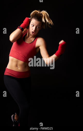 Front view of young woman shadow boxing with fists wrapped - Stock Image