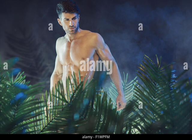 Tall and muscular guy in the rain forest - Stock Image