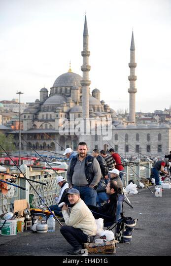 Turkey, Istanbul, Golden Horn, Fishermen on the Galata Bridge and Rustem Pasha Mosque (Rustem Pasa Camii) - Stock Image
