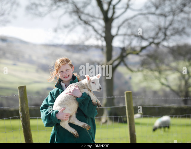 Child holding lamb smiling - Stock Image
