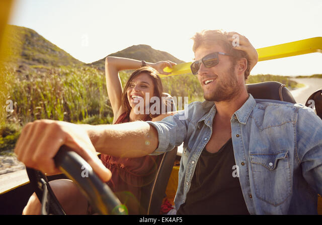 Cheerful young couple on road trip. Young man driving open topped car with woman smiling. - Stock-Bilder