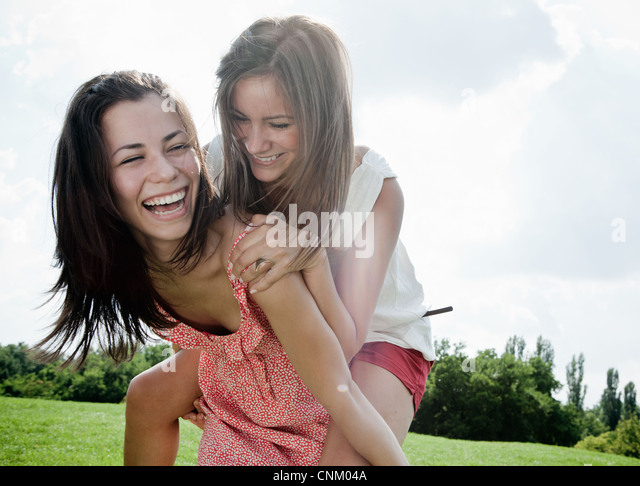 Smiling women playing outdoors together - Stock Image