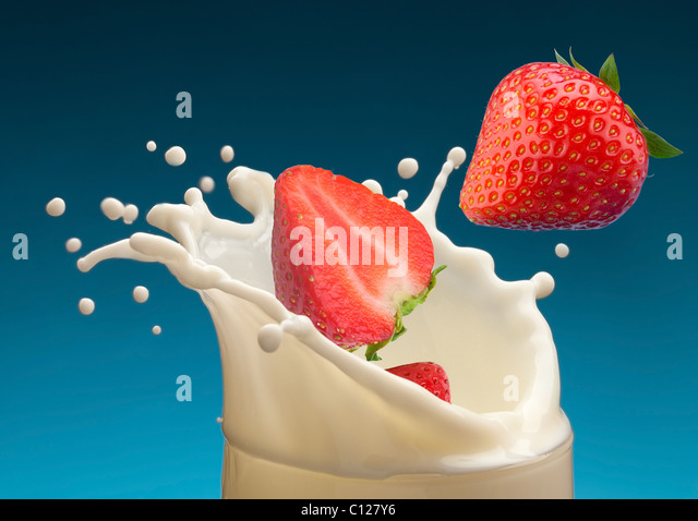 Splash of milk, caused by falling into a ripe strawberry. Isolated on a blue background. - Stock Image