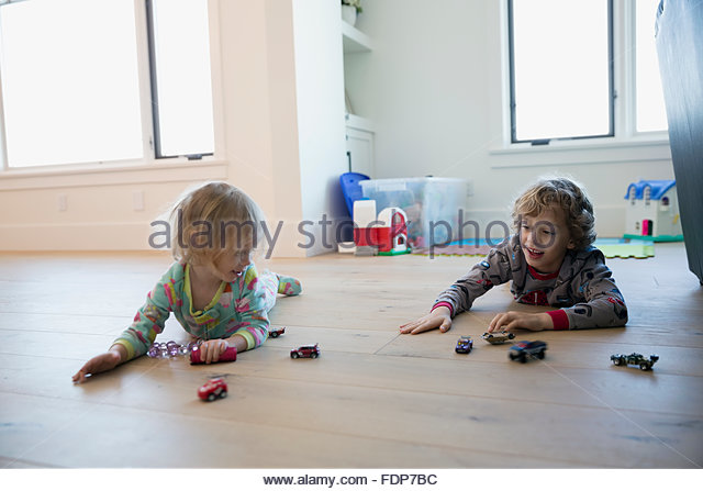 Brother and sister playing with toy cars floor - Stock Image