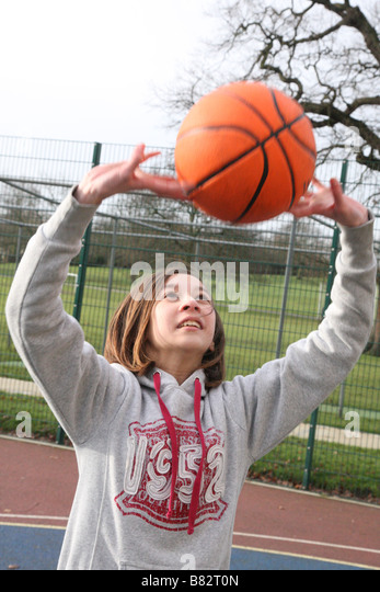 Teenage girl practicing netball in a park - Stock Image