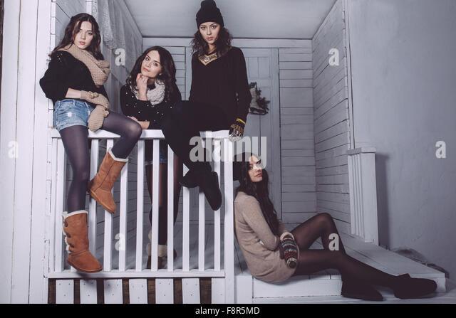 Four stylish models posing sitting on the fence - Stock-Bilder