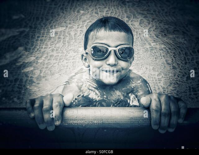 Portrait of an smiling boy with goggles in a swimming pool - Stock Image