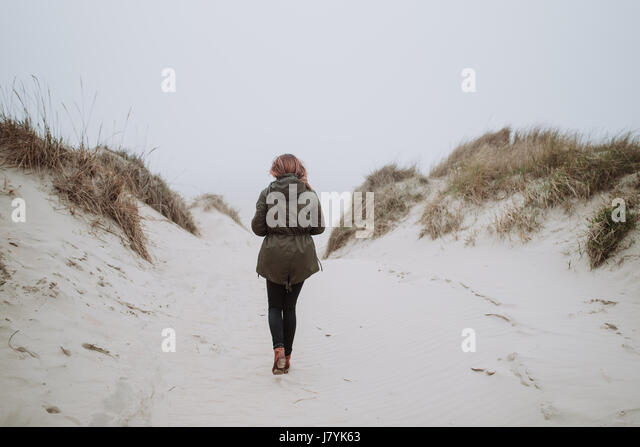 Woman walking on an empty beach in winter time - Stock Image