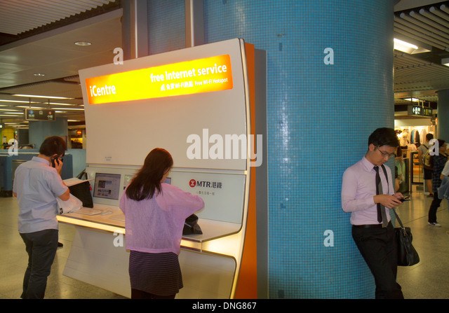 Hong Kong China Island MTR Admiralty Subway Station iCentre free Internet Asian man woman riders self-service kiosk - Stock Image