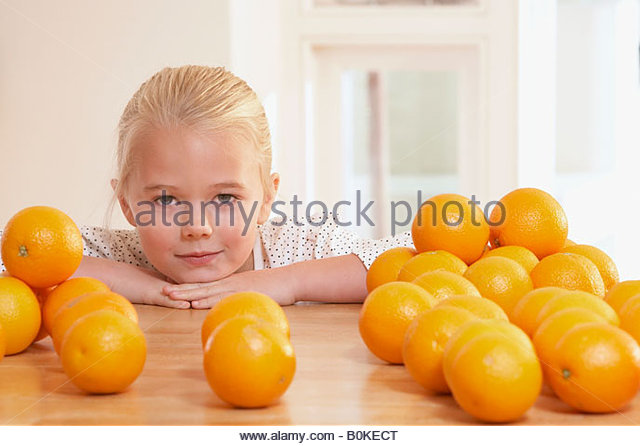Young girl in kitchen with lots of oranges on counter - Stock Image