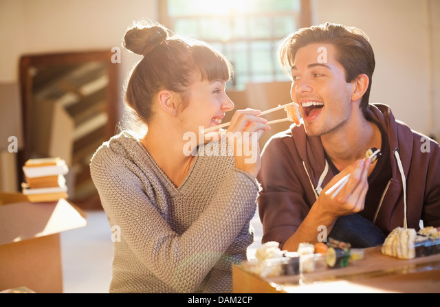 Couple eating sushi together in new home - Stock Image