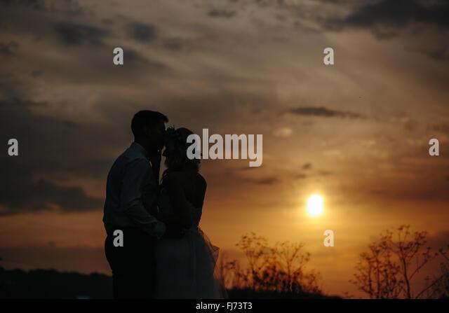 Silhouette of  wedding couple in field - Stock-Bilder