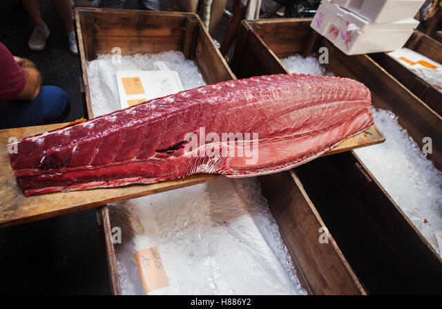 A traditional fresh fish market in Tokyo. A large fillet of tuna on a wooden board. catch of the day traditional - Stock Image