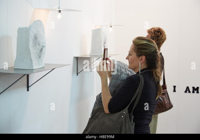 Woman shooting photos to a sculpture with a smartphone during Artissima, contemporary art fair opening - Stock Image
