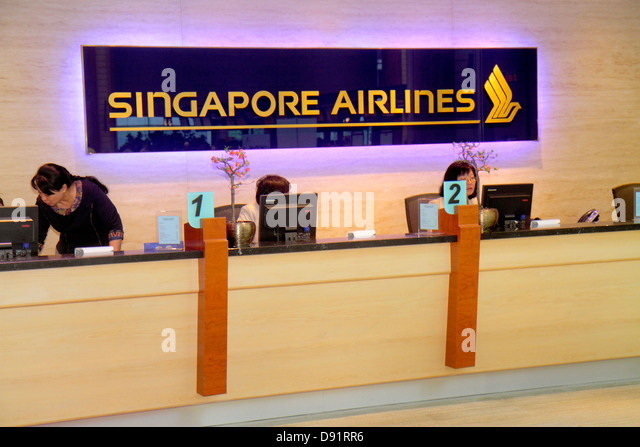 Singapore Changi International Airport SIN terminal concourse Asian woman Singapore Airlines customer service counter - Stock Image