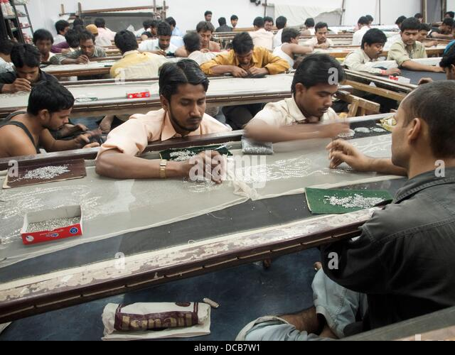 Workers place and sew beads and embellishments onto fabric in the Mumbai, India workshop/office of an Indian company - Stock-Bilder