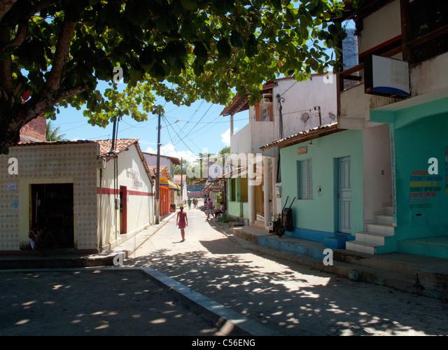 Girl walking down the street in the village of Velha Boipeba on Boipeba Island, Bahia State, Brazil - Stock Image
