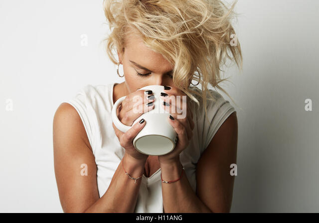 Portrait Young Blonde Head Female Perfect Skin Holding Hands White Cup Copy Space Wall Your Business Information - Stock Image